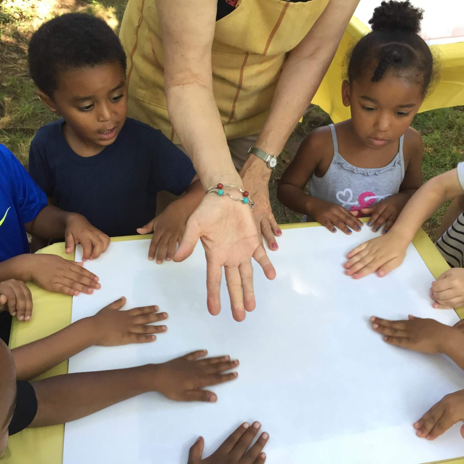 Young children gathered around a table getting ready to make an art project on a large, white piece of paper.