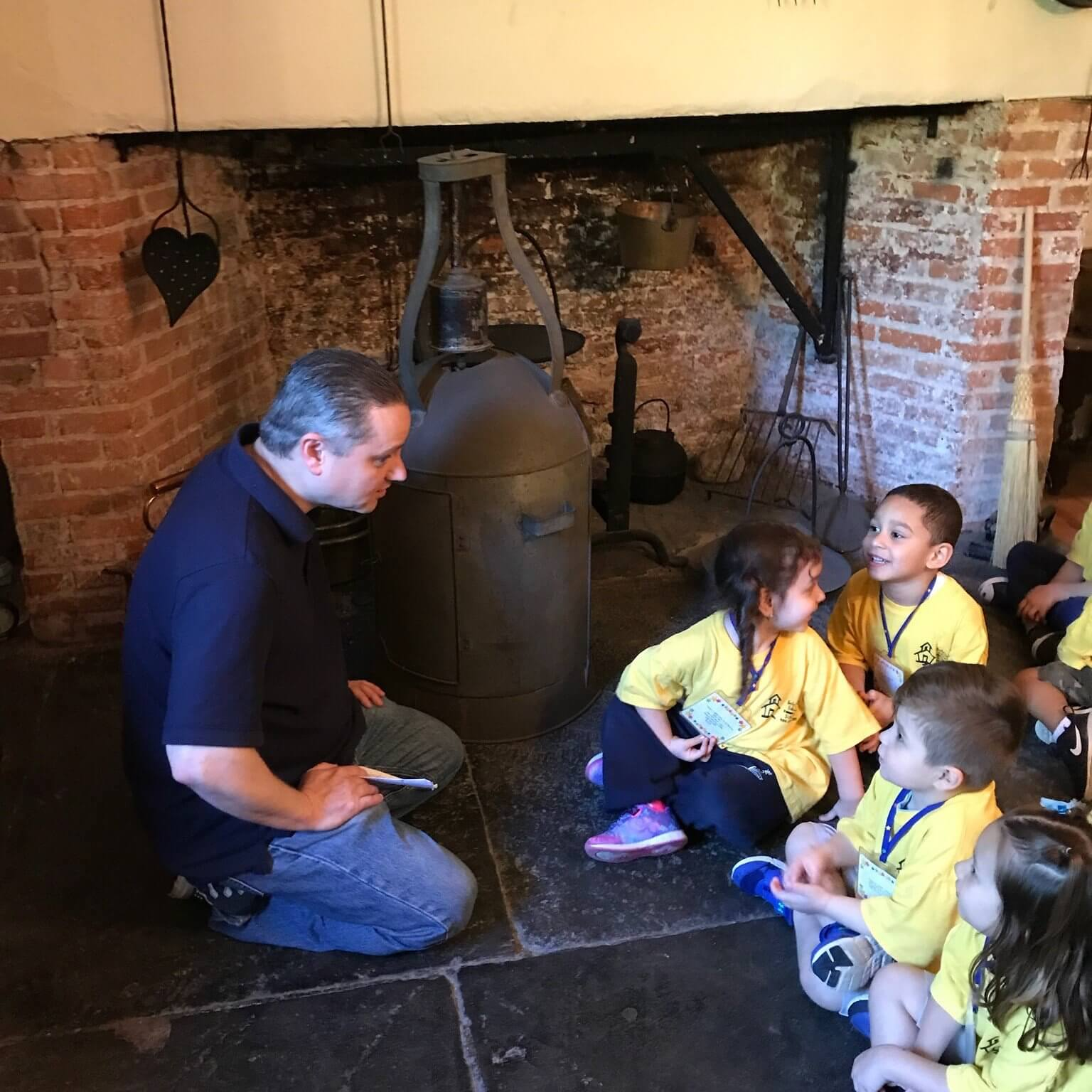 A group of young children wearing yellow t-shirts seated on the hearth in front of the antique fireplace. They are talking with a male curator.